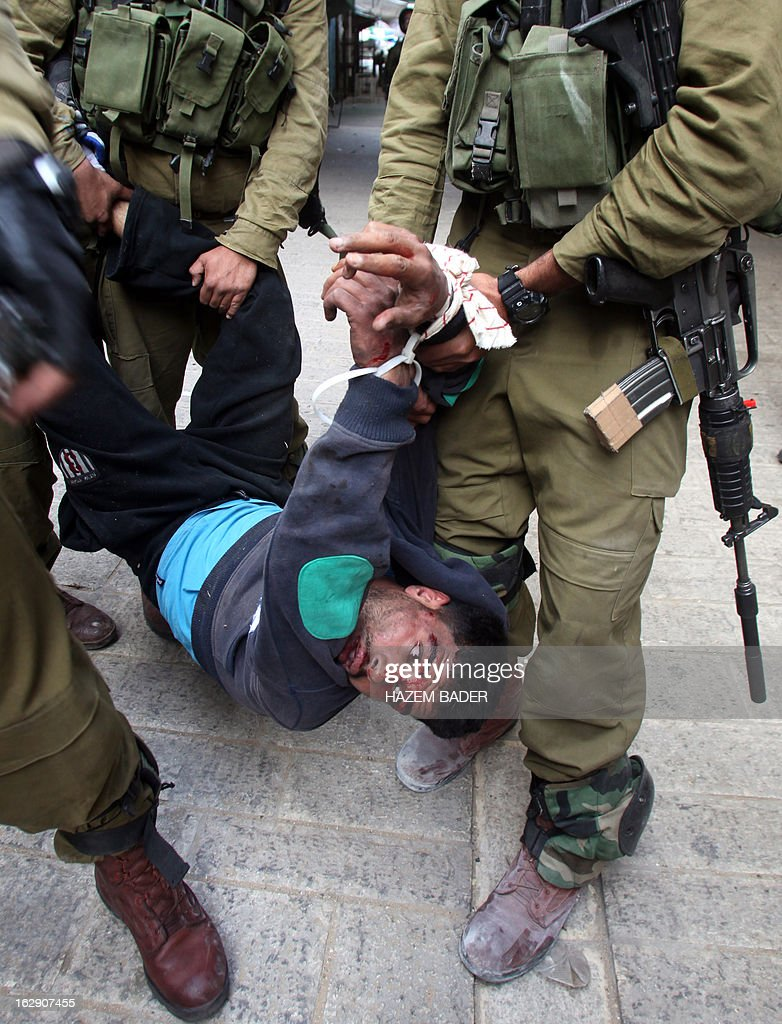 Israeli soldiers detain a Palestinian protester during clashes in the old city of Hebron on March 1, 2013 following a protest demanding the reopening of Shuhada Street, the one-time heart of the city. Flanked by a handful of Jewish settlement enclaves, the Shuhada Street was partially closed off in 1994 after local settler Baruch Goldstein opened fire on Muslim worshippers at the city's Al-Ibrahimi mosque, killing 29 of them. AFP PHOTO / HAZEM BADER