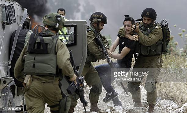 Israeli soldiers detain a Palestinian protester following a demonstration against the expropriation of Palestinian land by Israel in the West Bank...