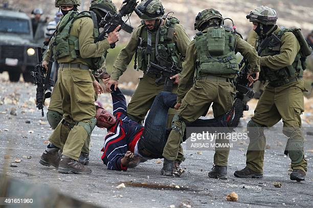 Israeli soldiers detain a wounded Palestinian stone thrower after infiltrated members of the Israeli security forces shot at fellow protesters during...