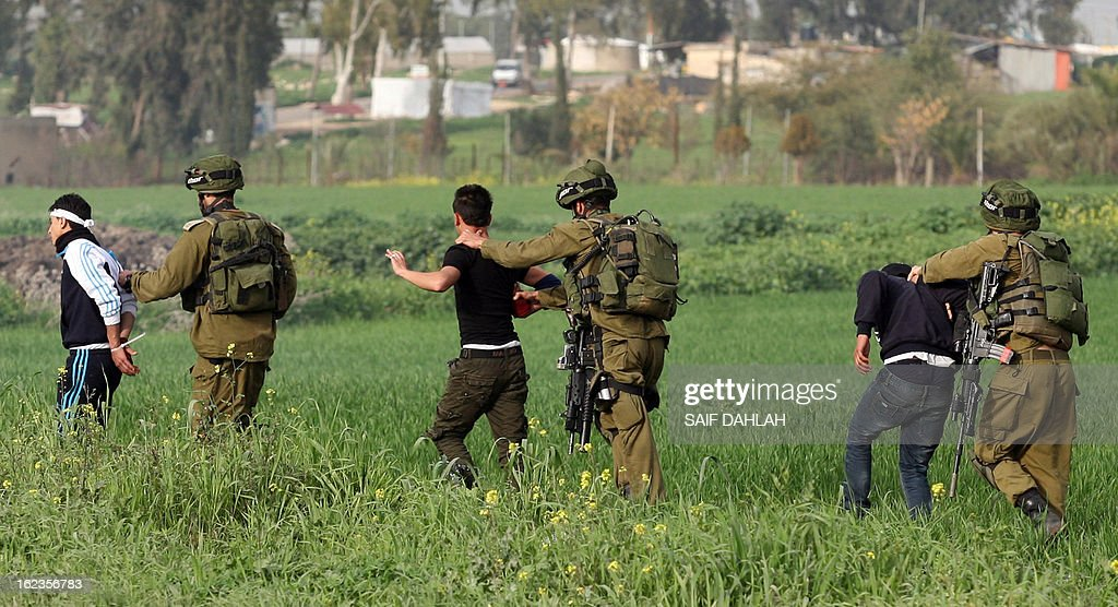Israeli soldiers detain Palestinian demonstrators following clashes at the entrance of the Jalama checkpoint, near the West Bank city of Jenin, on February 22, 2013. Palestinians demanding the release of hunger-striking prisoners clashed with Israelis in the West Bank and east Jerusalem, as three fasting inmates were taken to hospitals.