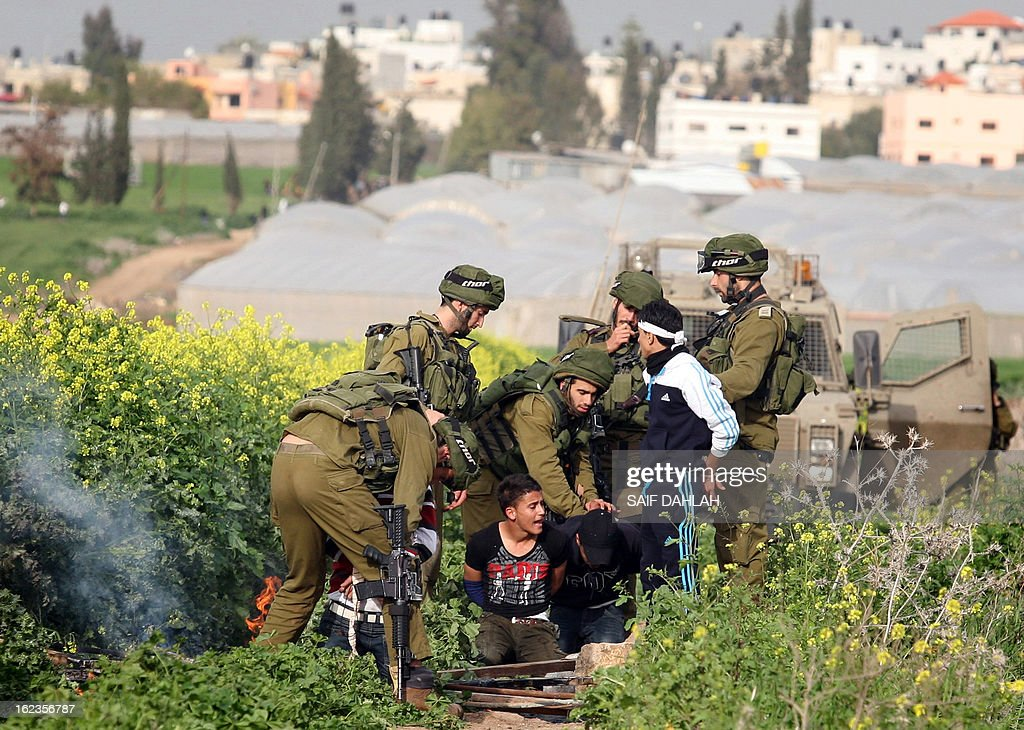 Israeli soldiers detain Palestinian demonstrators following clashes at the entrance of the Jalama checkpoint, near the West Bank city of Jenin, on February 22, 2013. Palestinians demanding the release of hunger-striking prisoners clashed with Israelis in the West Bank and east Jerusalem, as three fasting inmates were taken to hospitals. AFP PHOTO/SAIF DAHLAH