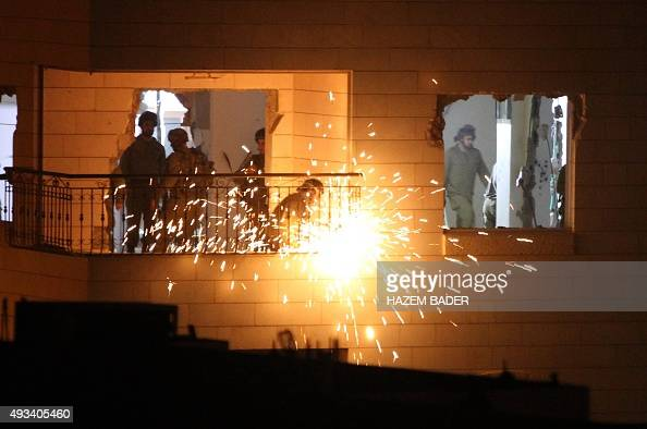Israeli soldiers dismantle the rail of a terrace after destroying the interior of an apartment home to Maher alHashlamoun a Palestinian jailed for...