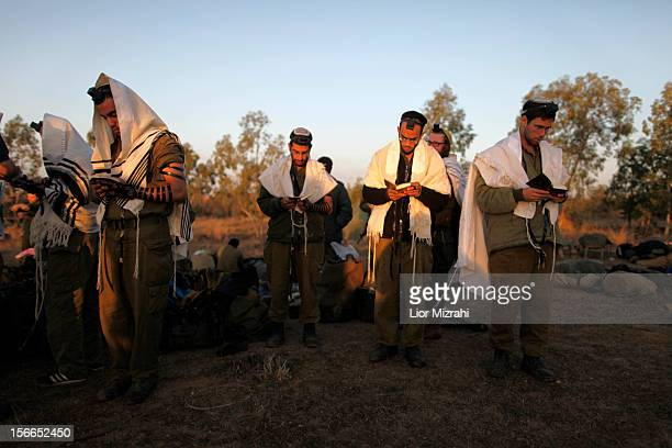 Israeli soldiers do their morning prayers in a deployment area on Israel's border with the Gaza Strip on November 18 in Israel Israeli shelling of...