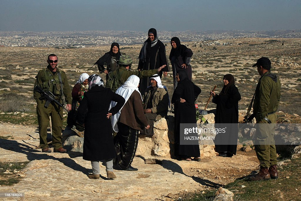Israeli soldiers evacuate Palestinian land owners trying to farm on their land near the Jewish settlement of Sosia, in the village of Yatta south of the West Bank city of Hebron on December 29, 2012. Palestinian farmers are restricted from cultivating their land in the disputed area near the city of Hebron due to the Israeli settlements and military zone nearby.