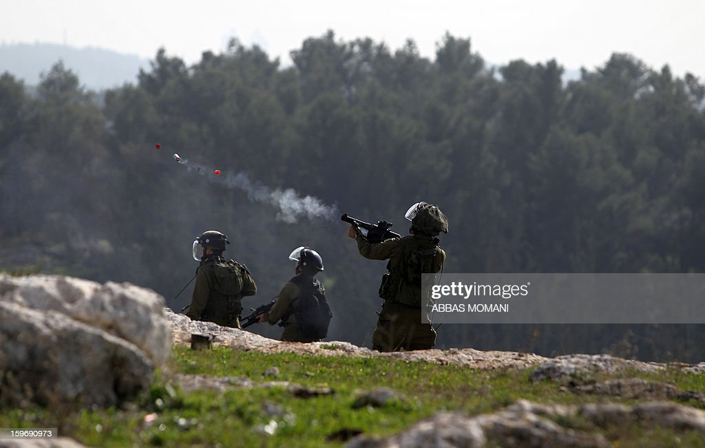 Israeli soldiers fire tear gas canisters at Palestinian protestors during a demonstration in the West Bank village of Budrus, on January 18, 2013. The Palestinians are bracing for a new right-wing government that Israel's election is expected to produce, hoping that international and domestic moves will strengthen their position. AFP PHOTO / ABBAS MOMANI