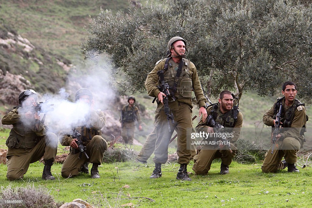 Israeli soldiers fire tear gas canisters towards Palestinian residents of the northern West Bank village of Madama, as they disperse clashing Palestinian farmers and Israeli settlers from the Yitzhar settlement, on December 17, 2012 in the Israeli-occupied West Bank, near Nablus. AFP PHOTO/JAAFAR ASHTIYEH