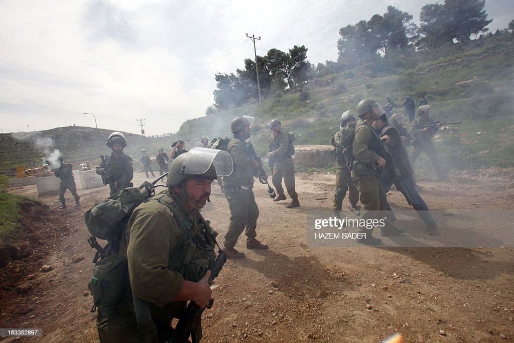 Israeli soldiers fire tear gas towards Palestinian protesters during clashes following a protest against the expropriation of Palestinian land by Israel on March 1, 2013, near the israeli settlement of Hagay in the West bank town of Hebron. AFP PHOTO/ HAZEM BADER