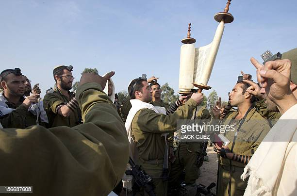 Israeli soldiers from a tank squadron wearing 'Talit' and 'Tefilin' hold a Torak scroll as they conduct morning prayers at an Israeli army deployment...