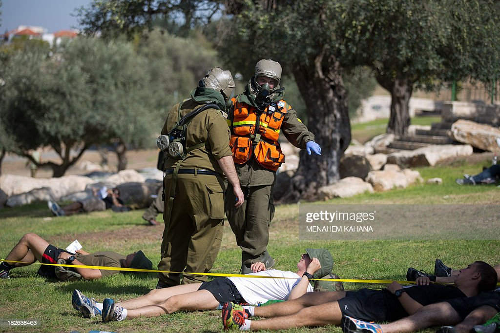 Israeli soldiers from the army's Home Front Command wearing chemical warfare suits take part in a defence drill simulating a chemical missile attack in the central Israeli city of Beit Shemesh, on October 2 2013.AFP PHOTO/MENAHEM KAHANA