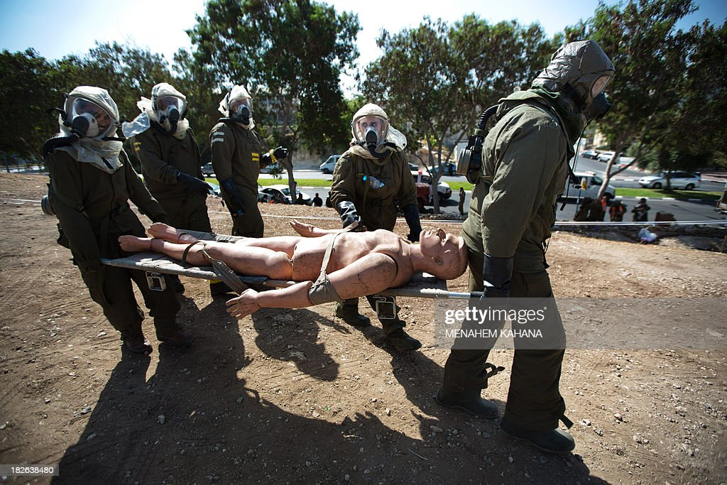 Israeli soldiers from the army's Home Front Command wearing chemical warfare suits carry a dummy of an injured man as they take part in a defence drill simulating a chemical missile attack in the central Israeli city of Beit Shemesh, on October 2 2013.