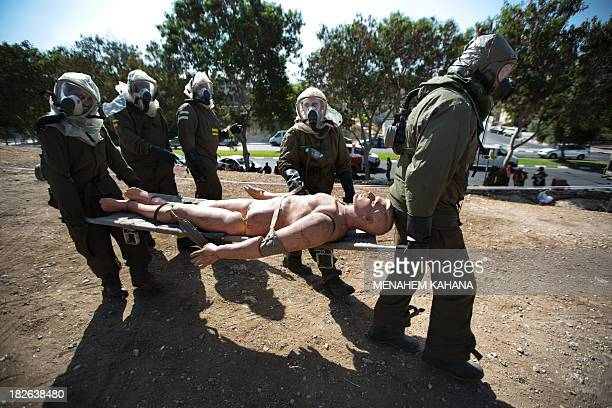 Israeli soldiers from the army's Home Front Command wearing chemical warfare suits carry a dummy of an injured man as they take part in a defence...