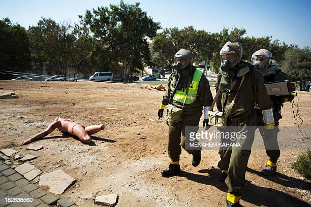 Israeli soldiers from the army's Home Front Command wearing chemical warfare suits take part in a defence drill simulating a chemical missile attack...