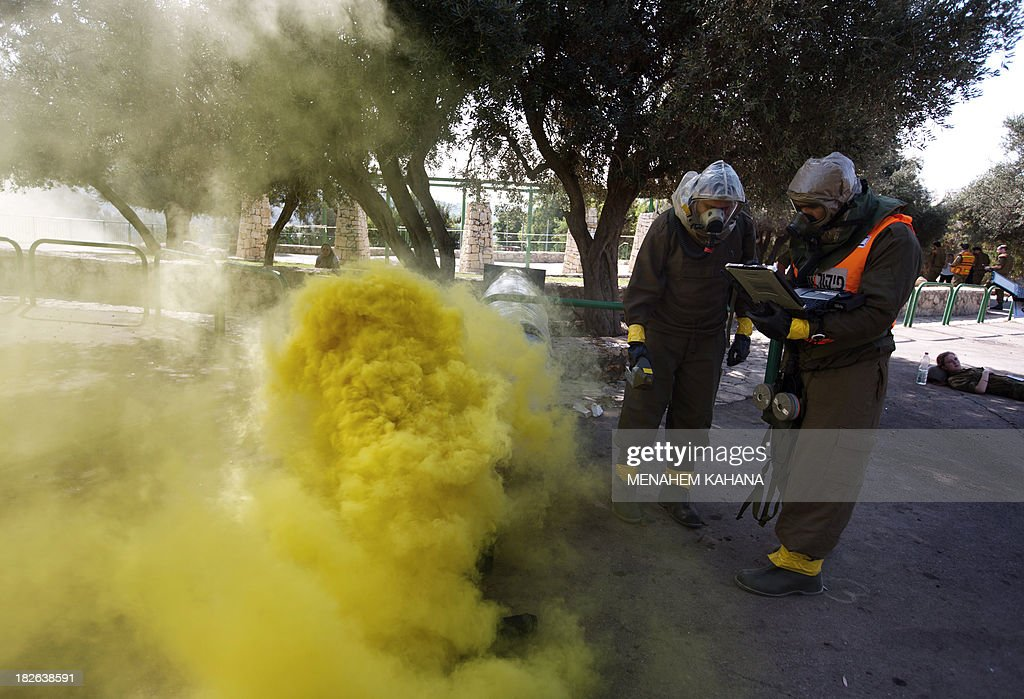 Israeli soldiers from the army's Home Front Command wearing chemical warfare suits take part in a defence drill simulating a chemical missile attack in the central Israeli city of Beit Shemesh, on October 2 2013.