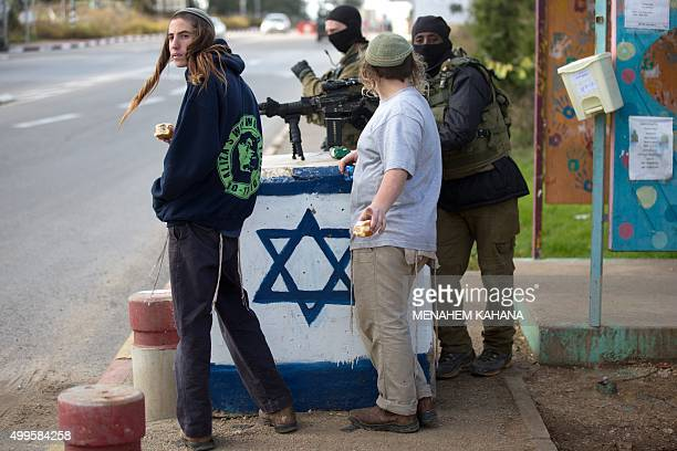 Israeli soldiers from the elite infantry unit stand guard as Israeli settlers stand at a bus station at the Gush Etzion junction in the Israeli...