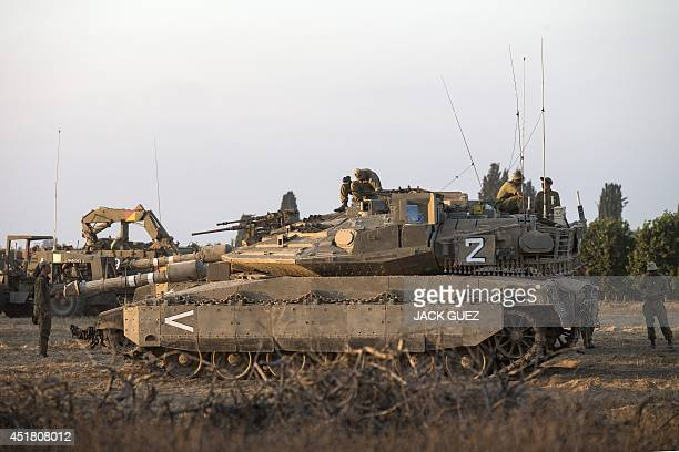 Israeli soldiers gather around Merkava tanks positioned on the Israeli side of the border with the Gaza Strip on July 7 2014 Militants in the Gaza...