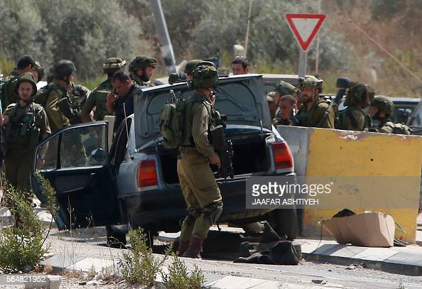 Israeli soldiers gather next to a vehicle belonging to a Palestinian man after he reportedly charged it into a group of soldiers at the Israeli army...