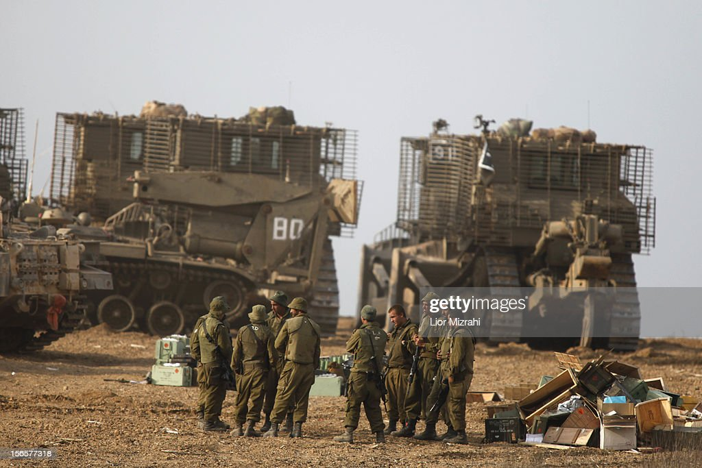 Israeli soldiers gather next to their armoured personnel carriers (APC) stationed on Israel's border with the Gaza Strip, on November 17, 2012, in Israel. At least 39 Palestinians and three Isreali's have died since conflict began four days ago. Israeli troops have been massing on the border as some 200 targets were hit overnight in Gaza, including Hamas cabinet buildings.