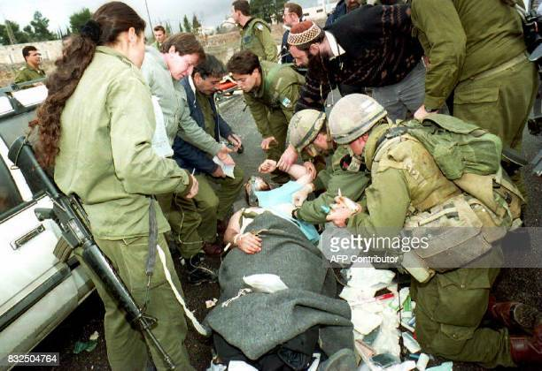 Israeli soldiers give first aid to a Jewish settler reportedly wounded by Palestinian gunmen 02 February 1994 in West Bank The gunmen opened...