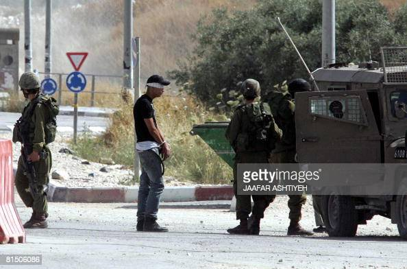 Israeli soldiers guard a blindfolded and handcuffed Palestinian youth after he was detained allegedly for carrying explosives on Hawara checkpoint...