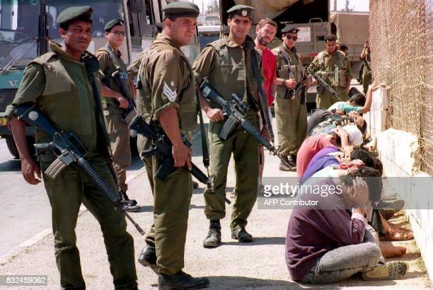 Israeli soldiers guard Palestinians roundedup 06 August 1993 after the murder last night of an Israeli soldier in this West Bank village near...