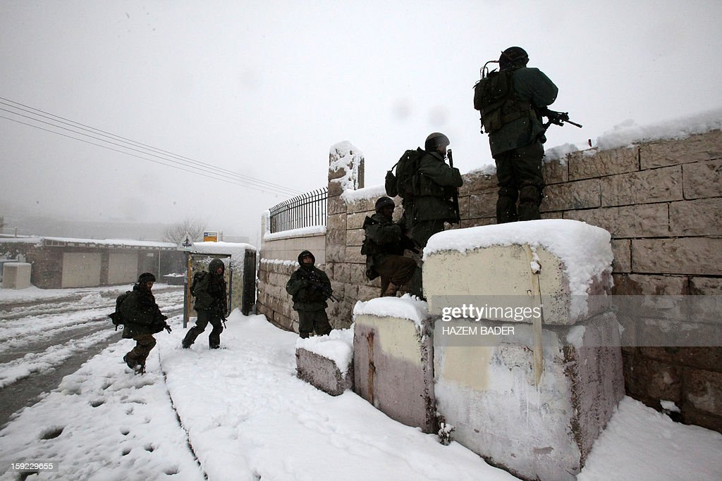 Israeli soldiers guard the Israeli settlers zones despite of the snow on January 10, 2013 in the West Bank city of Hebron. As temperatures plummeted, the bitter winds and rain that have battered the Middle East since Sunday turned into snow, blanketing Jerusalem in white and closing schools and businesses, as much of the transport infrastructure ground to a halt. AFP PHOTO / HAZEM BADER
