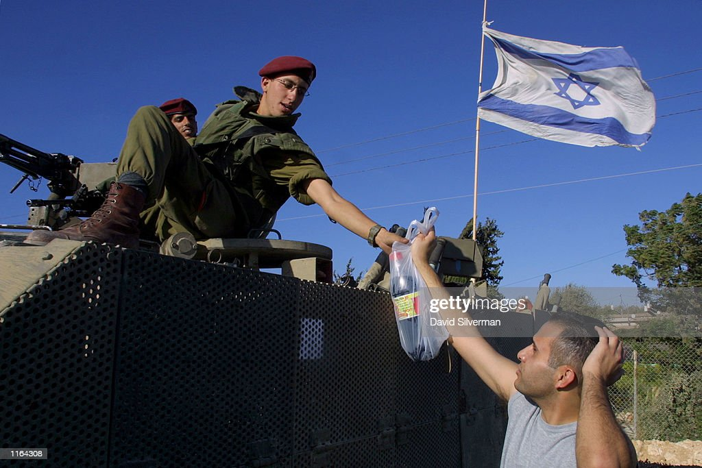 Israeli soldiers, guarding a highway from the West Bank into Jerusalem near the Palestinian village of el-Jib, receive a gift from a passing Israeli motorist, September 28, 2001. Israeli security remains high despite a ceasefire agreement one year after Palestinian unrest broke out.