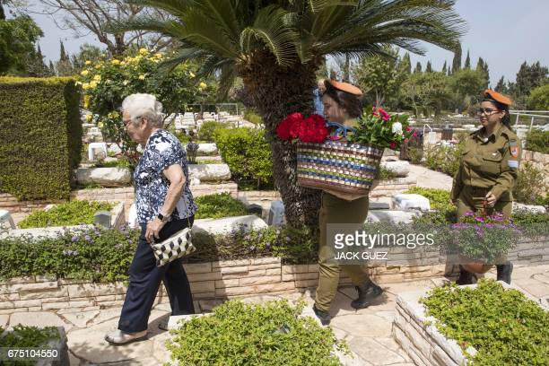 Israeli soldiers help a woman as she visits the grave of a relative at the Kiryat Shaul military cemetery as the country starts to mark the memorial...