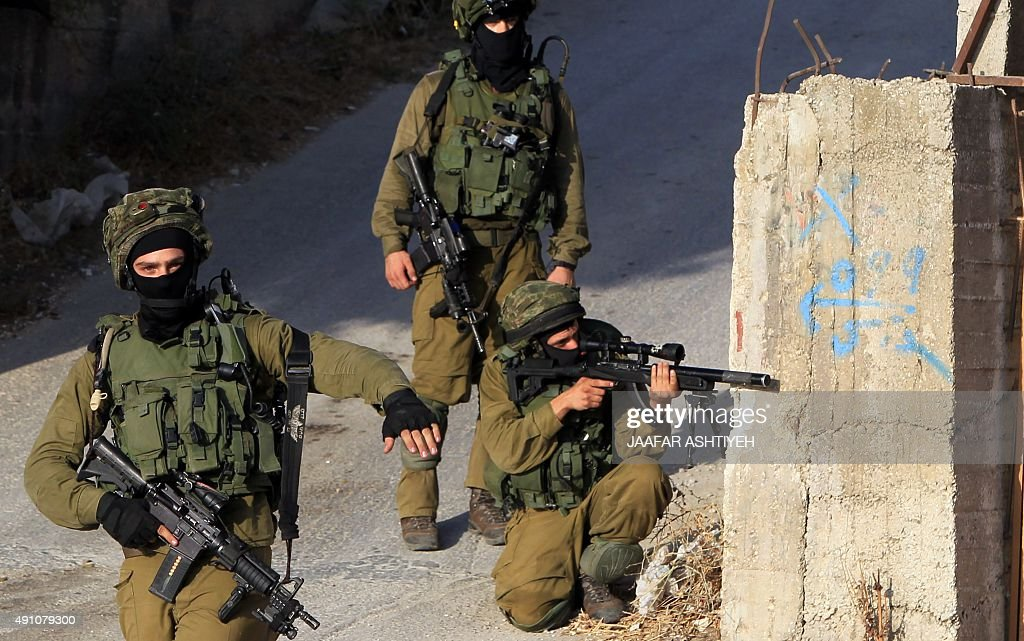 Israeli soldiers hold a position in a street east of the West Bank city of Nablus on October 3 as they search for the suspected Palestinian killers...