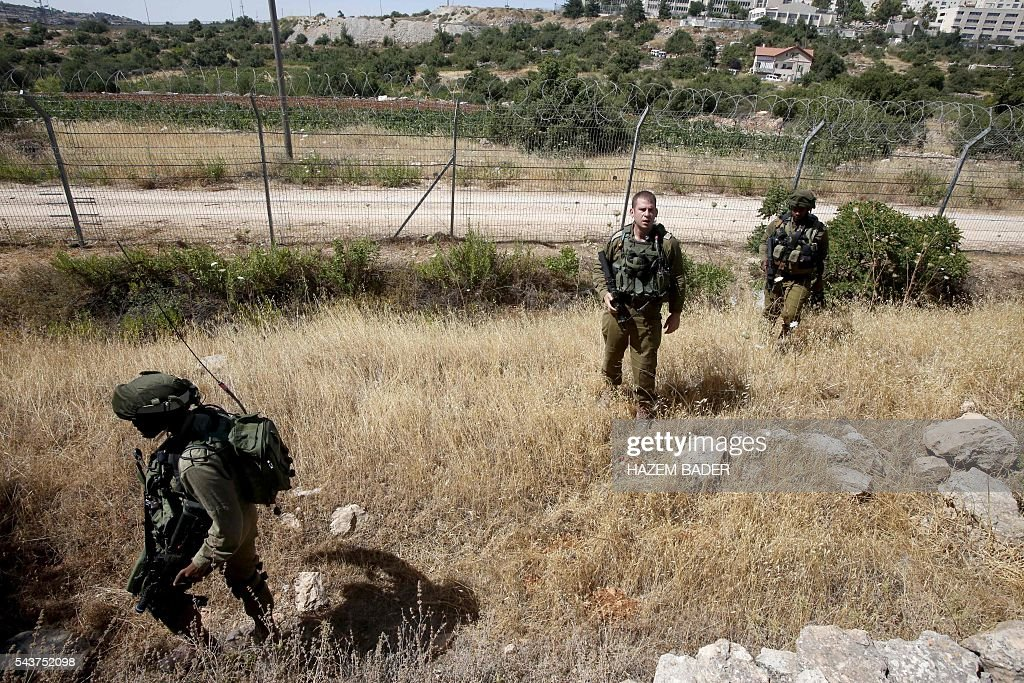 Israeli soldiers inspect a fence in the Jewish settlement of Kiryat Arba where a 13-year-old Israeli girl was fatally stabbed in her bedroom on June 30, 2016 in the occupied West Bank near the Palestinian city of Hebron. A Palestinian attacker broke into the Jewish settlement in the occupied West Bank, fatally stabbing a teenage girl and wounding a security guard before being shot dead, the army said. BADER