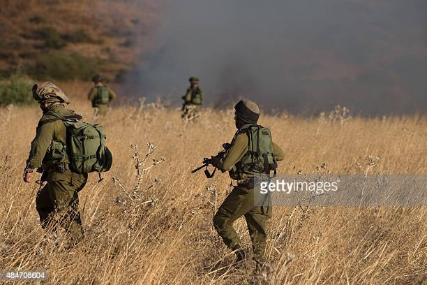 Israeli soldiers inspect a field where rockets fired from Syria landed near Kfar Szold causing fires but no injuries in northern Israel close to the...