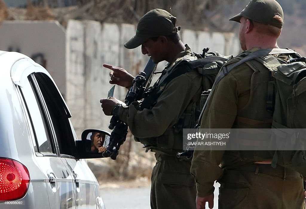 Israeli soldiers inspect a Palestinian car at a checkpoint close to the West Bank village of Beit Furik east of Nablus on October 2 after Palestinian...