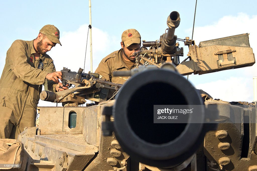 Israeli soldiers inspect the machine gun of a Merkava tank stationed in the Israeli-occupied Golan Heights along the border with Syria on July 17, 2013. Gunmen from Syria infiltrated a disused army outpost in the Israeli-occupied area of the Golan Heights just beyond the ceasefire line, a military spokeswoman said. The incident came a day after several mortar rounds hit the Israeli side of the Golan, causing several fires to break out along the ceasefire line as Syrian rebels battled regime forces near the Quneitra crossing. AFP PHOTO/JACK GUEZ
