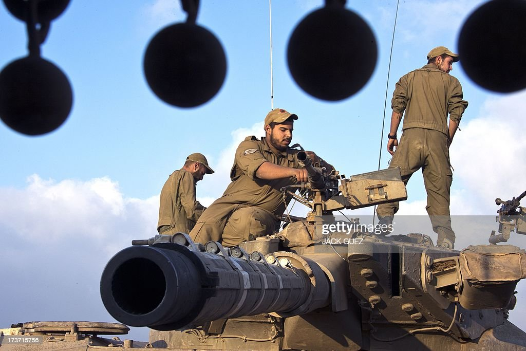 Israeli soldiers inspect the machine gun of a Merkava tank stationed in the Israeli-occupied Golan Heights along the border with Syria on July 17, 2013. Gunmen from Syria infiltrated a disused army outpost in the Israeli-occupied area of the Golan Heights just beyond the ceasefire line, a military spokeswoman said. The incident came a day after several mortar rounds hit the Israeli side of the Golan, causing several fires to break out along the ceasefire line as Syrian rebels battled regime forces near the Quneitra crossing.