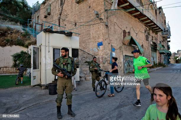 Israeli soldiers keep guard as children of Israeli settlers play outside the Beit Hadassah Jewish settlement in the divided West Bank city of Hebron...
