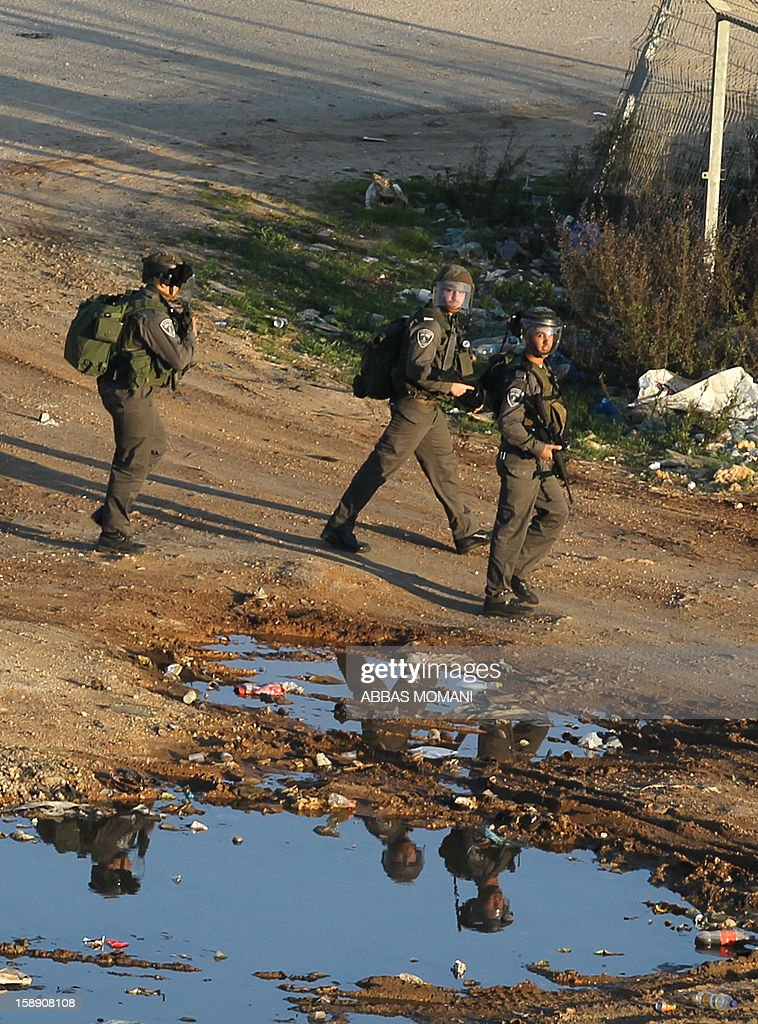 Israeli soldiers keep guard as Palestinian youths throw stones using sling shots towards them at the entrance to Israel's Ofer military prison, near the West Bank village of Betunia, following a demonstration in support of Palestinian prisoners on hunger strike in Israeli jails and calling for their immediate release on January 3, 2013.