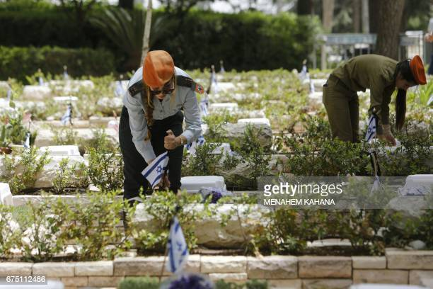 Israeli soldiers lay flowers on the graves of fallen soldiers at the Mount Herzel military cemetery in Jerusalem on April 30 a few hours ahead of the...