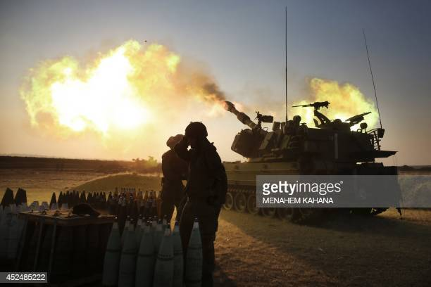 Israeli soldiers of the 155mm artillery cannons unit fire towards the Gaza Strip from their position near Israel's border with the coastal...