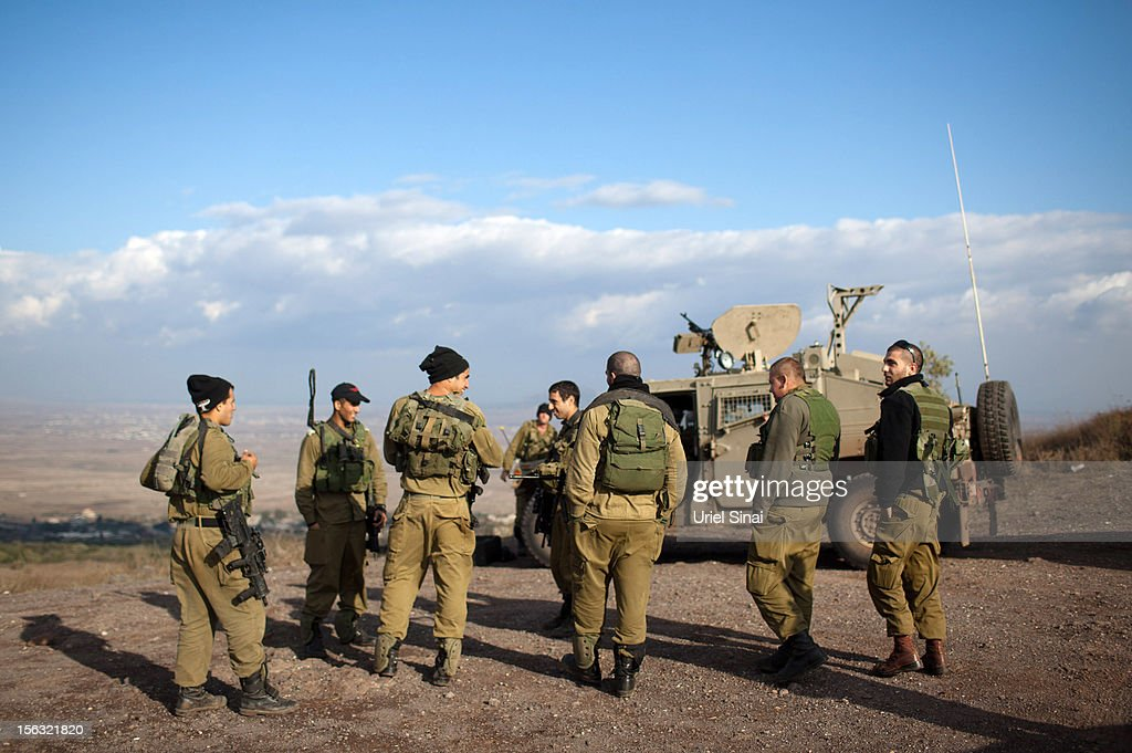 Israeli soldiers on the border line with Syria at the Israeli-annexed Golan Heights overlooking the Syrian village of Breqa on November 13, 2012 near Alonei Habashan in the Golan Heights. Tension remains high in the disputed Golan Heights after Israeli Defence Forces retaliated after mortar shells were fired into Israeli territory from Syria.