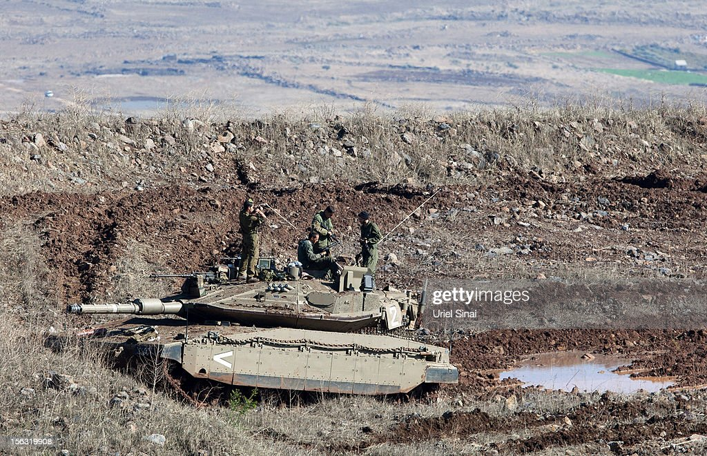 Israeli soldiers on top of a Merkava tank as they take a position on the border line with Syria at the Israeli-annexed Golan Heights, overlooking the Syrian village of Breqa on November 13, 2012 in the Golan Heights. Tension remains high in the disputed Golan Heights after Israeli Defence Forces retaliated after mortar shells were fired into Israeli territory from Syria.