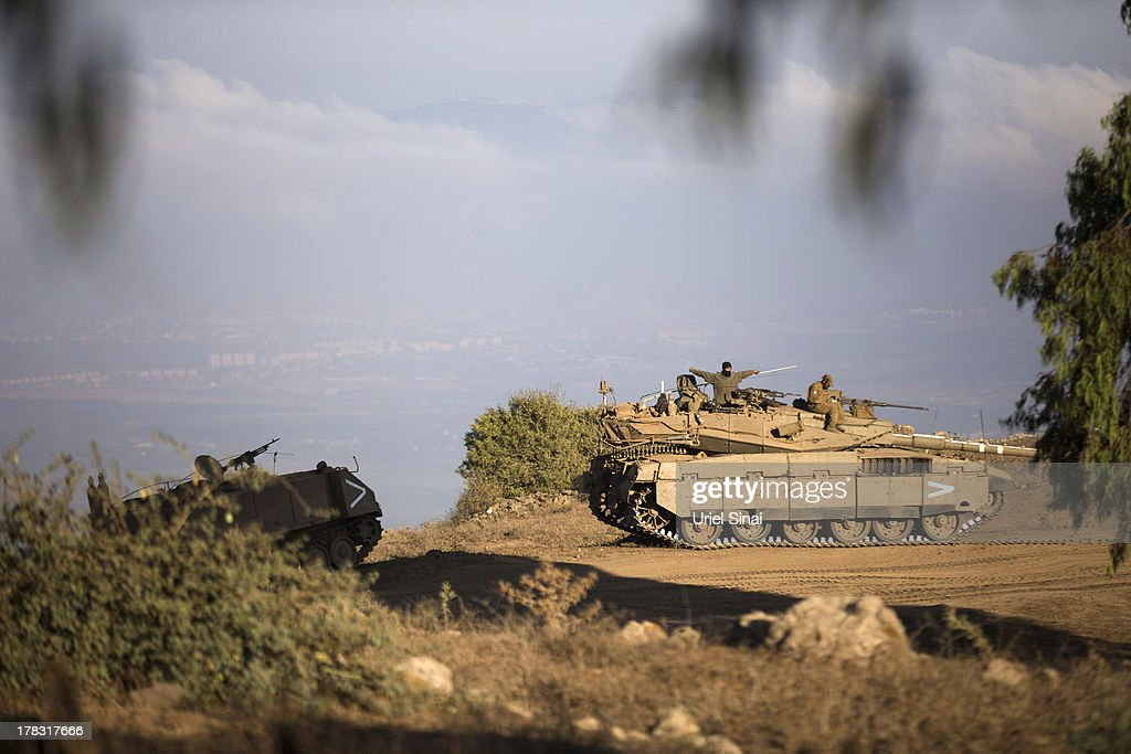 Israeli soldiers on top of their tank during a military exercise on August 29, 2013 near the border with Syria, in the Israeli-annexed Golan Heights.Tension's are rising in Israel amid international talks of a military intervention In Syria.