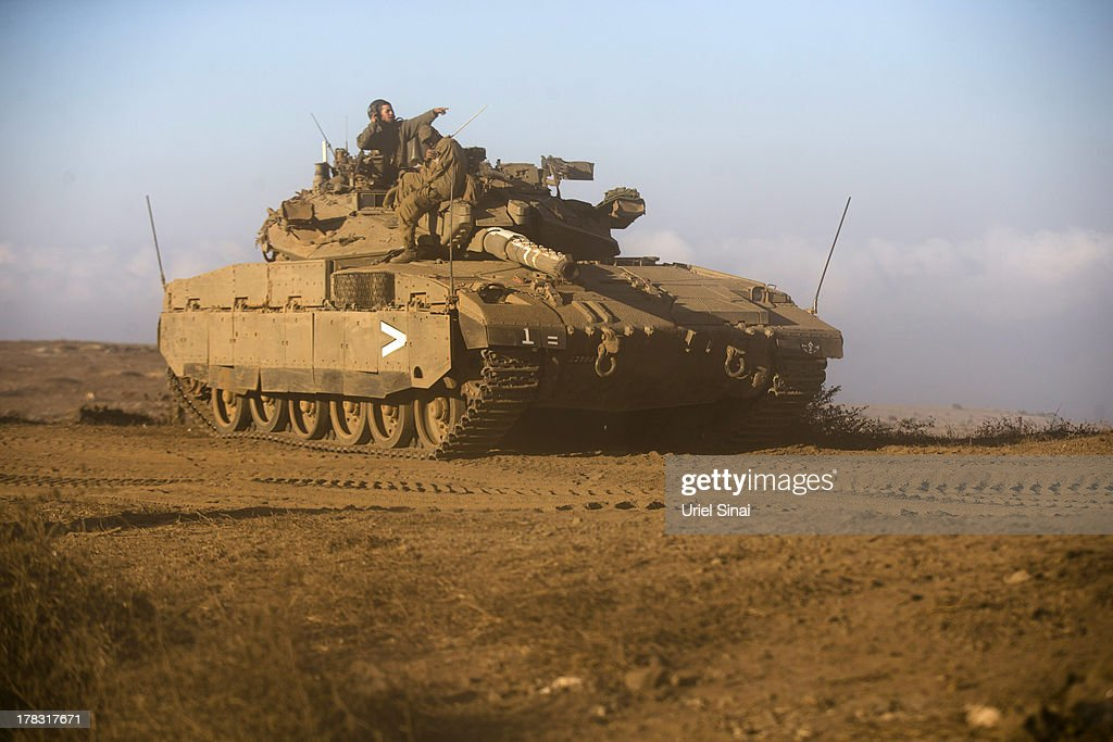 Israeli soldiers on top of their tank during a military exercise on August 29, 2013 near the border with Syria, in the Israeli-annexed Golan Heights. Tension's are rising in Israel amid international talks of a military intervention In Syria.
