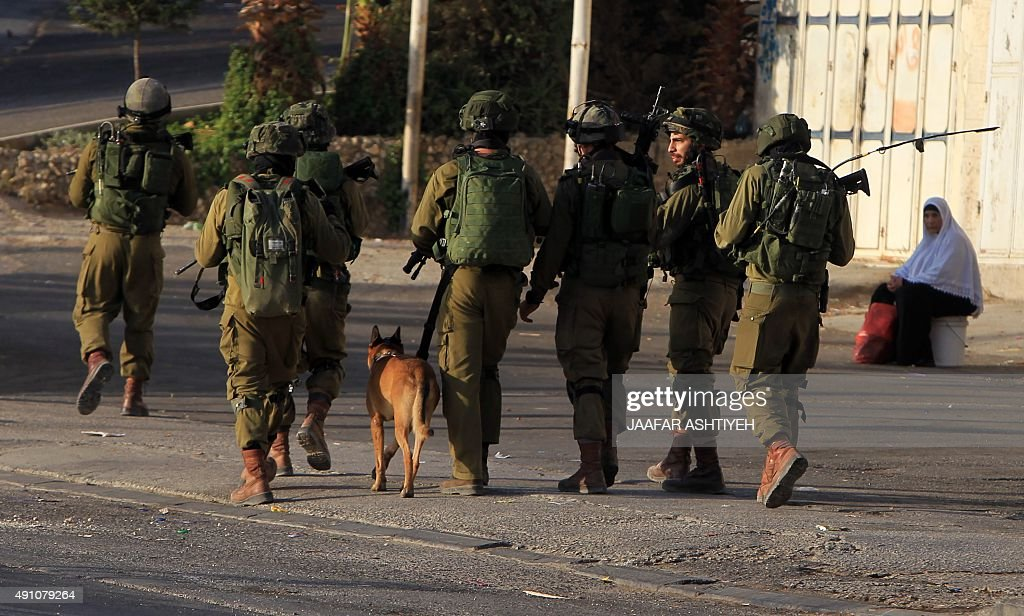 Israeli soldiers patrol a street east of the West Bank city of Nablus on October 3 as they search for the suspected Palestinian killers of a Jewish...