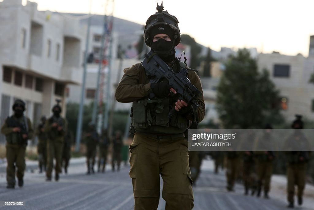 Israeli soldiers patrol a street in the northern West Bank village of Salem, east of Nablus, during an operation to arrest wanted Palestinians early on May 30, 2016. / AFP / JAAFAR