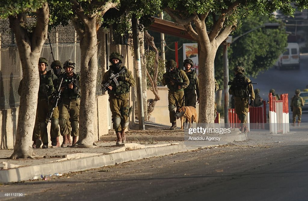 Israeli soldiers patrol in the West Bank city of Nablus as they search for the suspected Palestinian killers of two Jewish settlers on October 03...