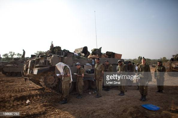 Israeli soldiers perform their morning prayers in a deployment area on November 19 2012 on Israel's border with the Gaza Strip The death toll has...