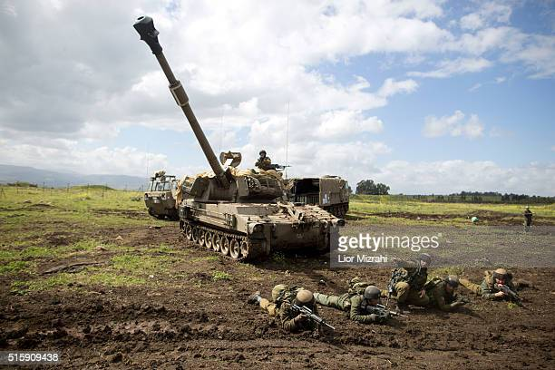 Israeli soldiers practice next to a selfpropelled gun during an army drill on March 16 2016 in Israeliannexed Golan Heights Israeli President Reuven...