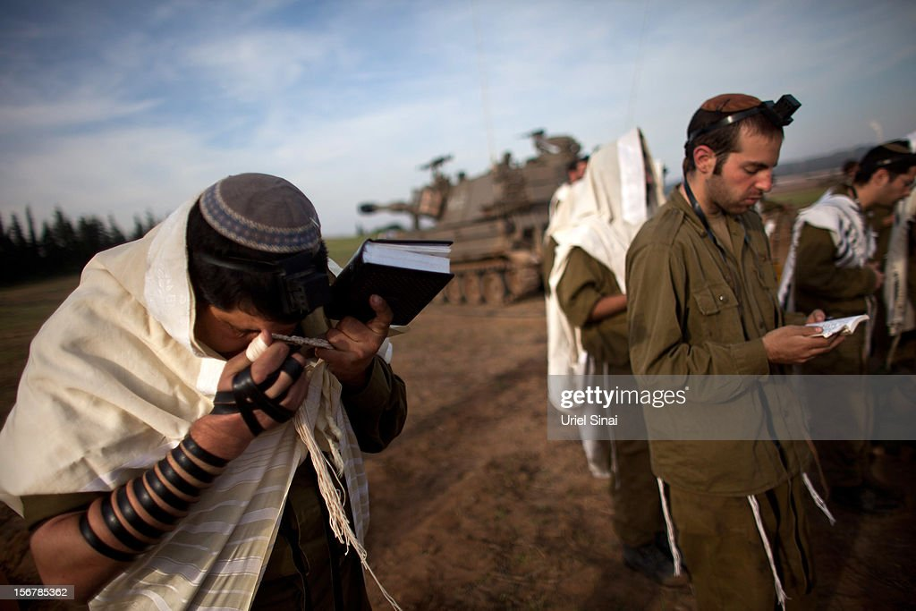 Israeli soldiers pray next to an artillery gun on November 21, 2012 on Israel's border with the Gaza Strip. Despite widespread rumours of a ceasefire militants in the Gaza Strip continue to fire rockets and Israel continues it's bombardment. US Secretary of State Hillary Clinton has arrived in Israel to support and encourage a peace deal being brokered by Egypt.