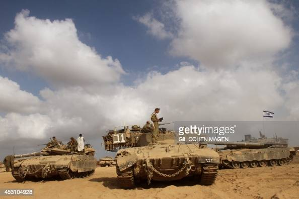 Israeli soldiers pray on top of their Merkava tanks along the border between Israel and the Gaza Strip after they pulled out from the Gaza Strip on...