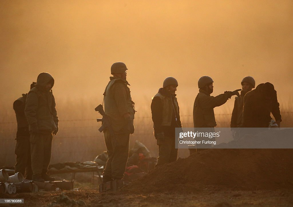 Israeli soldiers prepare a shell amongst smoke as an artillery emplacement fires into Gaza on November 21, 2012 on Israel's border with the Gaza Strip. Despite widespread rumors of a ceasefire, militants in the Gaza Strip continue to fire rockets and Israel continues its bombardment. US Secretary of State Hillary Clinton has arrived in Israel to support and encourage a peace deal being brokered by Egypt.