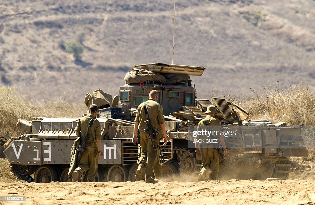Israeli soldiers prepare their Armoured Personnel Carrier (APC) in a training field in the Golan Heights, next to the Israeli-Syrian border, on October 10, 2013. The Israeli army fired on October 9, a Tammuz missile across the Syrian border in response to mortar fire from the Syrian at an Israeli military base in the northern Israeli-annexed Golan Heights leaving two soldiers with light wounds.